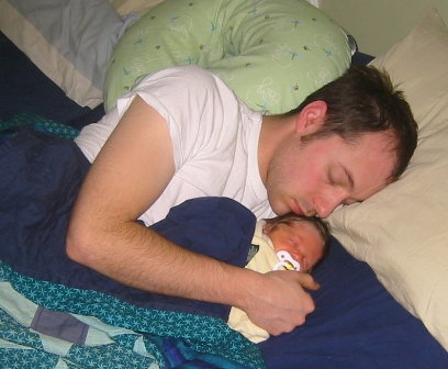 new father sleeping with newborn baby